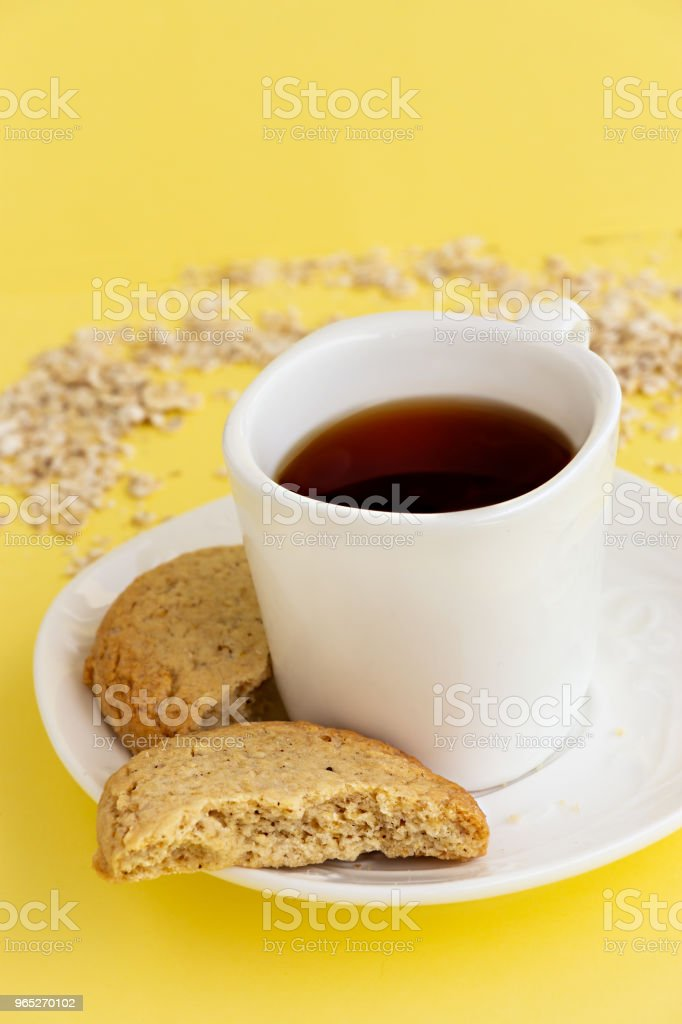 Gluten free homemade oats oatmeal cookies and cup of tea or coffee espresso on pastel yellow background. Copy space. royalty-free stock photo
