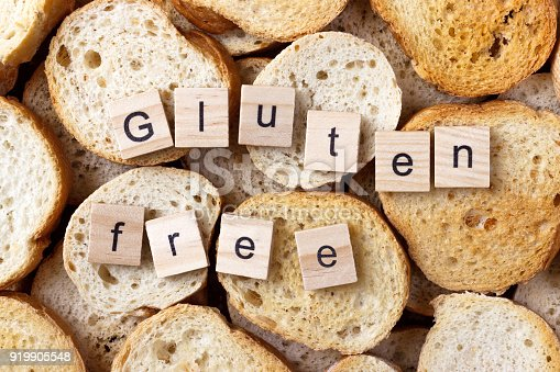 istock gluten free text on Background from many small round rusks. Top view 919905548