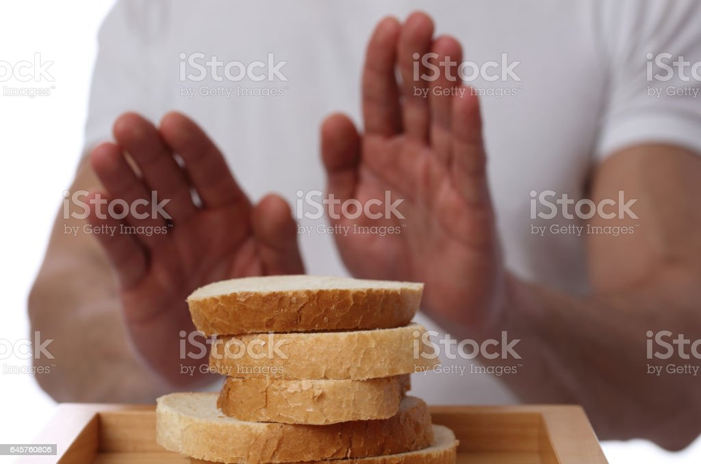 Gluten intolerance and diet concept. Man refuses to eat white bread. stock photo