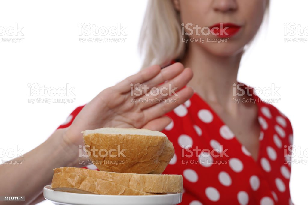 Gluten intolerance and diet concept. Woman refuses to eat white bread stock photo