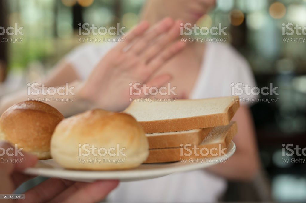 Gluten intolerance and diet concept. Woman refuses to eat white bread. Selective focus on bread stock photo