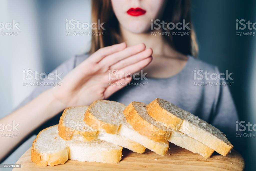 Gluten intolerance and diet concept. Young girl refuses to eat white bread stock photo