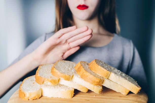 gluten intolerance and diet concept. young girl refuses to eat white bread - impasto per il pane foto e immagini stock