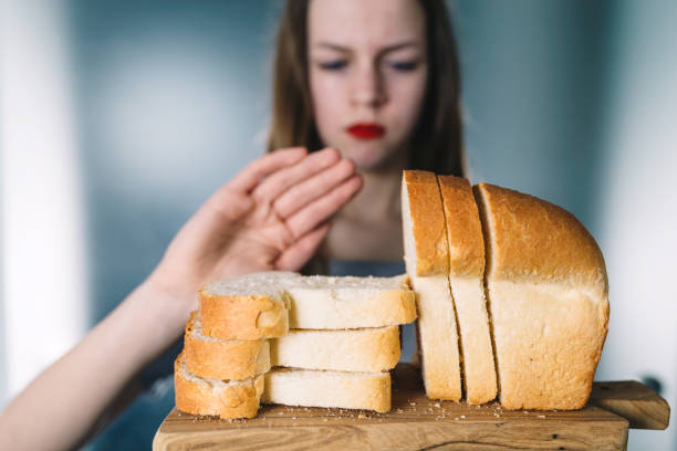 Gluten intolerance concept. Young girl refuses to eat white bread - shallow depth of field stock photo