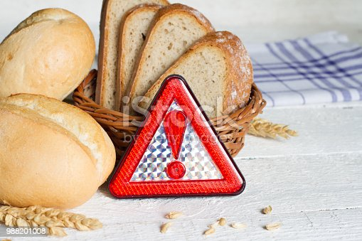 Gluten intolerance with bread wheat and warning sign on white planks closeup