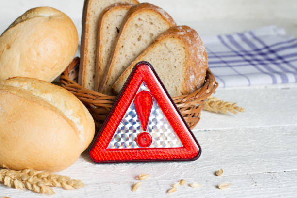 Gluten intolerance with bread wheat and warning sign on white planks stock photo