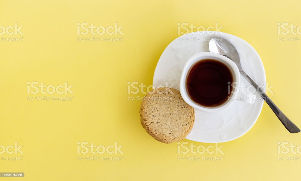 Glutenfree homemade oats oatmeal cookies and cup of tea or coffee espresso on pastel yellow background. Top view. Copy space. zbiór zdjęć royalty-free