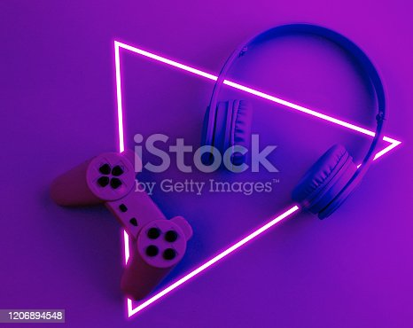 istock Gmer concept. Gamepad with headphones. 80's synth wave and retrowave glowing triangle futuristic aesthetics. Old fashioned abstraction concept 1206894548