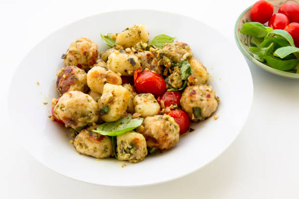 Gnocchi and chicken meatballs with pesto sauce and tomatoes stock photo