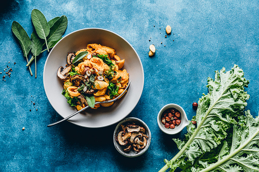 Gnocchi pasta with a pumpkin, mushroom and hazelnuts. Pumpkin pasta meal served in a bowl on blue table.