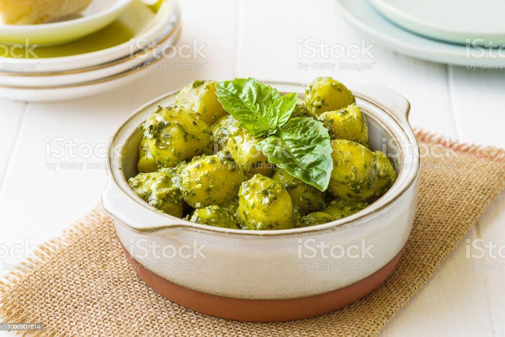 Gnocchi with 'Pesto' sauce, in terracatta bowl, on white woodwn background. x - foto stock