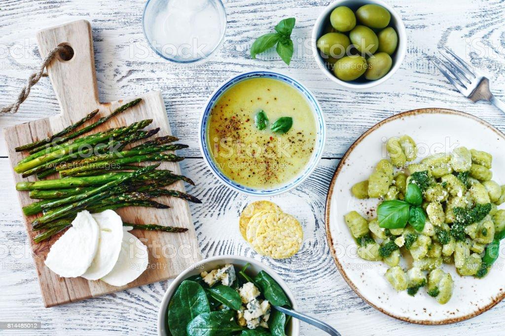 Gnocchi mit Pesto, Spinat-Salat mit Blauschimmelkäse, gebackene Spargel mit Mozzarella, grünem Püree, Suppe und Oliven – Foto