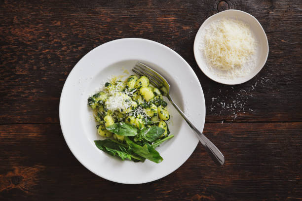 Gnocchi with spinach and parmesan Gnocchi with spinach and parmesan parmesan cheese stock pictures, royalty-free photos & images