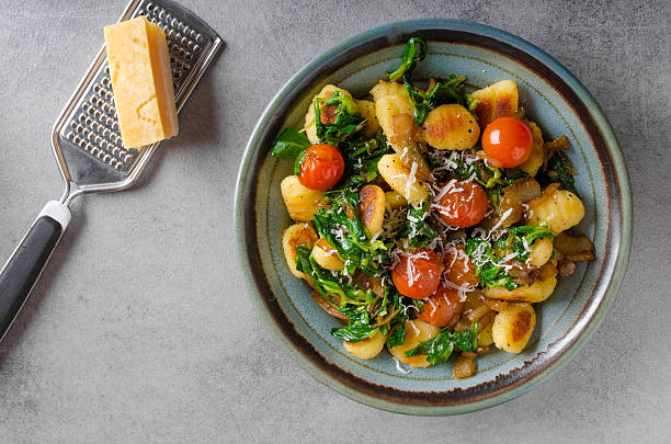 Gnocchi with spinach, garlic and tomatoes stock photo
