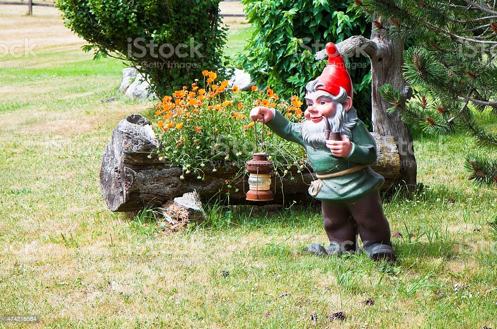 Gnome holding a lantern and smoking a pipe stock photo