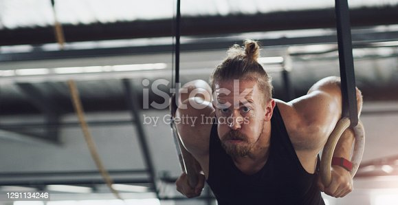 Shot of a young man exercising with gymnastic rings in a gym