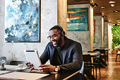 Portrait of positive stylish young Afro American businessman in dark-blue jacket and glasses sitting at the table, indoors, wearing wireless earbuds, chatting with his boss via video conference call using tablet pc, looking at the screen and smiling cheerfully