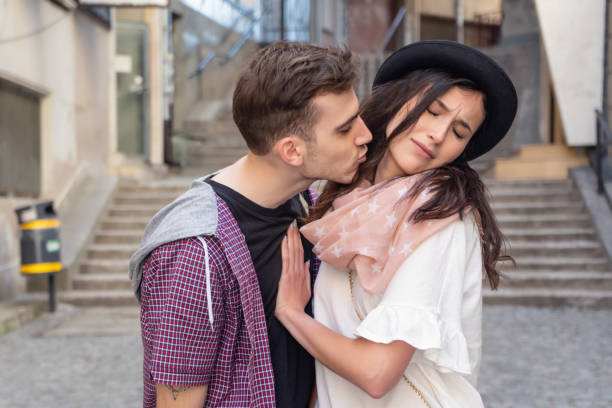 Go away A young male is leaning in to kiss his girlfriend but she is pushing him away and frowning. They are in a city, dressed in casual clothes. She is wearing a hat. bad date stock pictures, royalty-free photos & images
