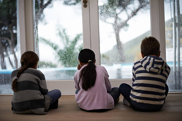 go away rain! come back another day - boy looking out window stock pictures, royalty-free photos & images