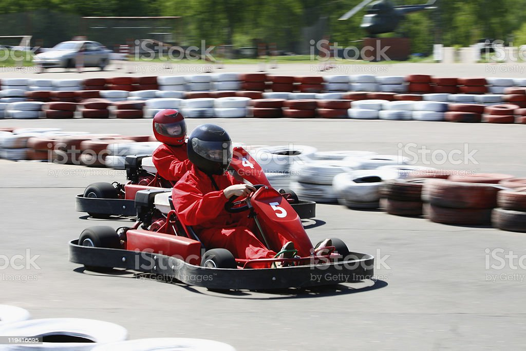 Go carts with drivers wearing red racing on a course royalty-free stock photo
