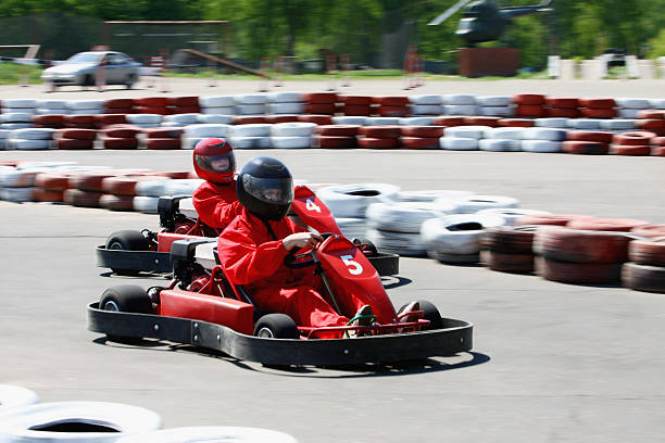 Go carts with drivers wearing red racing on a course stock photo