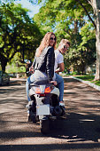 Rearview shot of a young attractive couple riding a scooter around town
