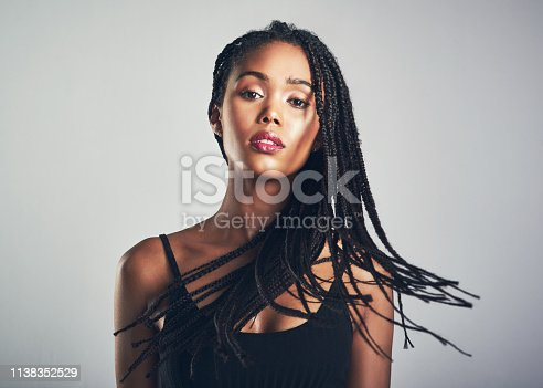 Shot of a beautiful young woman posing against a grey background