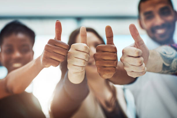 Go get that success! Cropped shot of a team of colleagues showing thumbs up at work achievement stock pictures, royalty-free photos & images