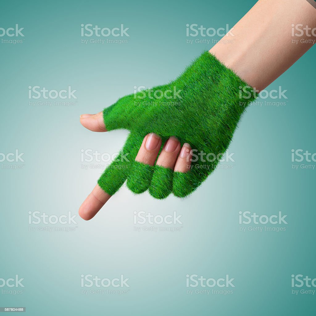 Go Green Concept Hand in glove grass indicates the direction. stock photo