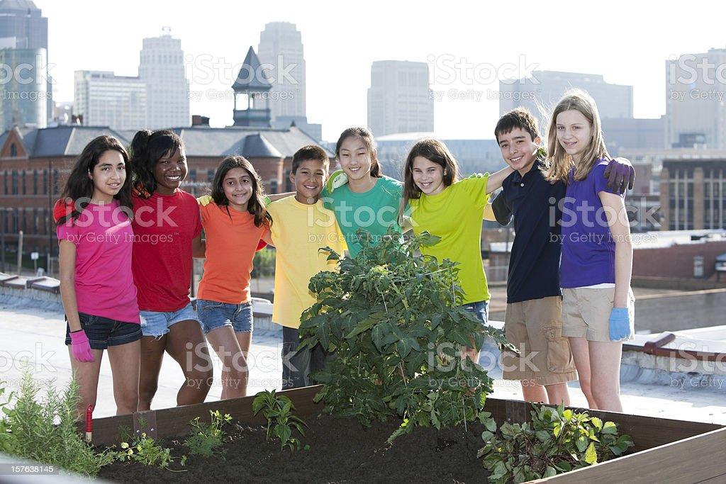 Go Green: Ethnically Diverse Children by Urban Roof Top Garden stock photo