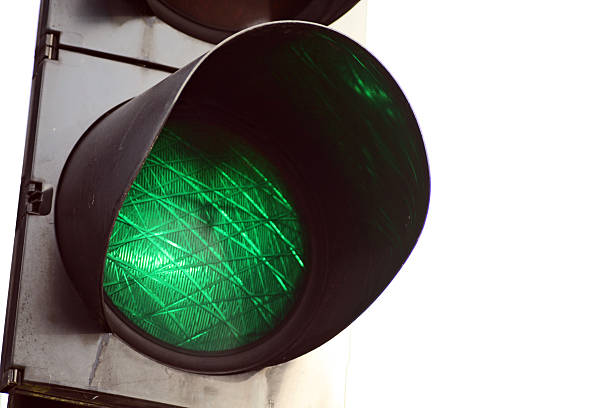Go - green light traffic signal on white background Green light on a traffic signal. pejft stock pictures, royalty-free photos & images