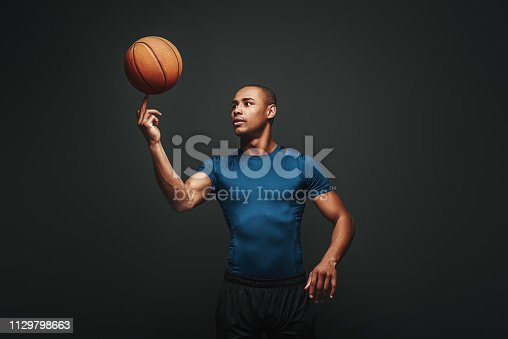Basketball player in blue T-shirt and black shorts spinning ball on his finger isolated on dark background