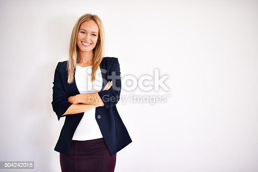 Portrait of an attractive woman standing with her arms crossed