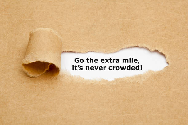 Go The Extra Mile Its Never Crowded Motivational quote Go The Extra Mile It's Never Crowded appearing behind ripped brown paper. dedicated stock pictures, royalty-free photos & images