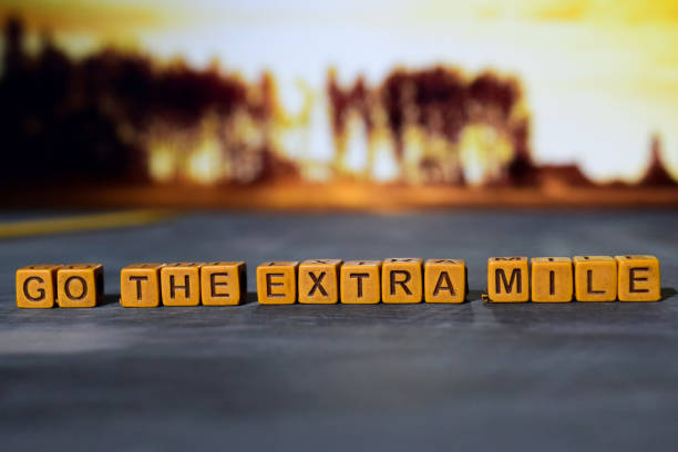 go the extra mile on wooden blocks. - dedication stock photos and pictures