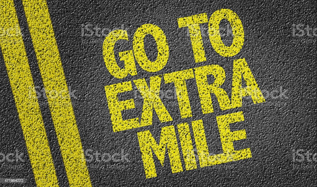 Go To Extra Mile written on the road stock photo