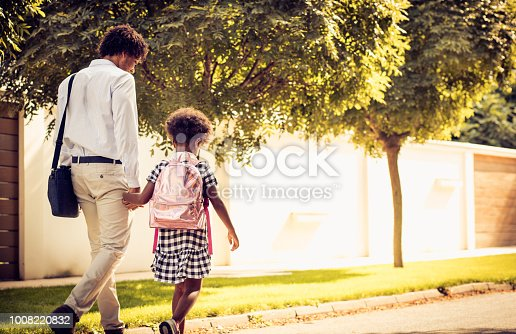 African American father and his daughter walking trough park. From back.