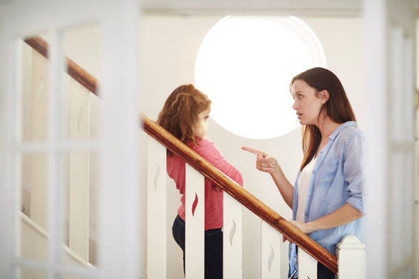 Go to your room and think about what you've done Shot of a mother disciplining her young daughter at home scolding stock pictures, royalty-free photos & images