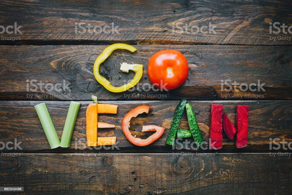 ビーガン野菜フラット置く暗い木製のテーブル トップ ビューにレタリングを行きます。栄養給食食材。ニースのポストカード、ポスター、バナーを調理します。 ストックフォト