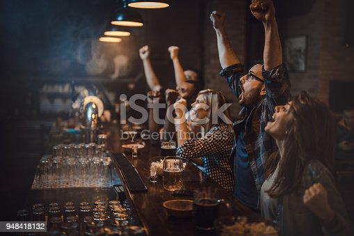Large group of excited fans celebrating success of their sports team while watching a game in a bar.