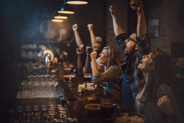 Goaaaaaaal! Large group of excited fans celebrating success of their sports team while watching a game in a bar. sport stock pictures, royalty-free photos & images