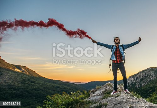 Young handsome hiker with open arm holds a singnal smoke flare