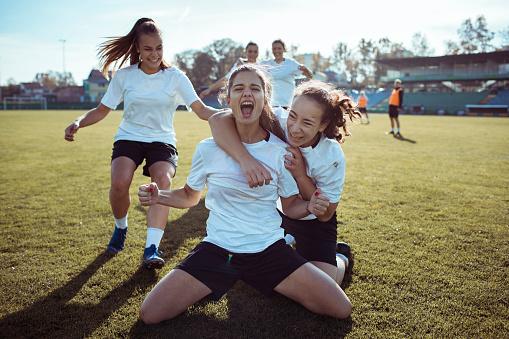Close up of a female soccer team celebrating a scored goal