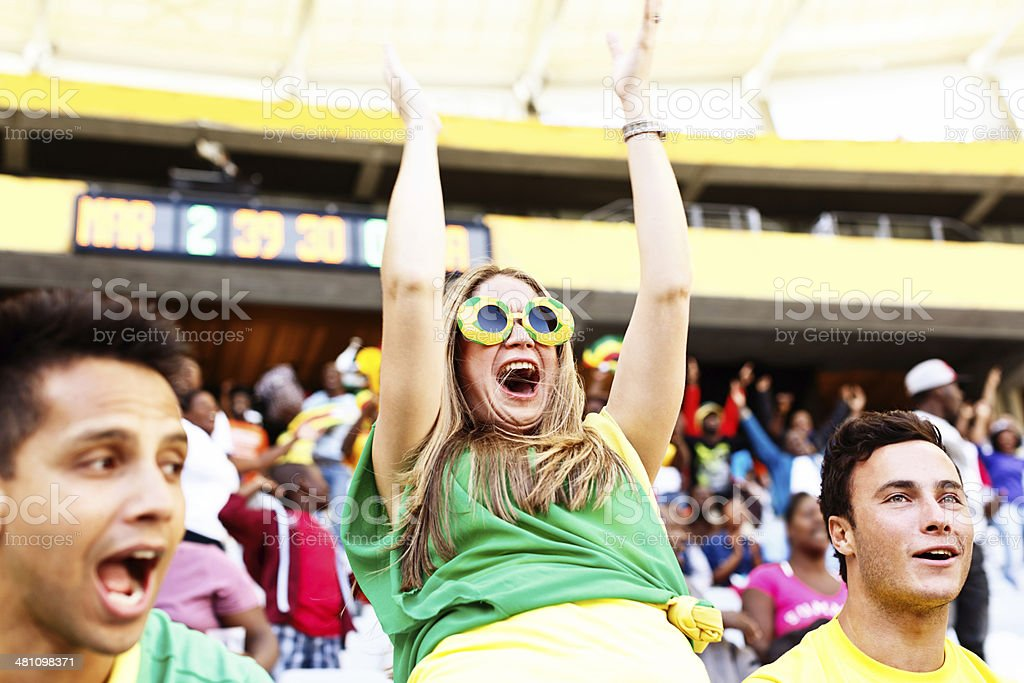 Goal! Ecstatic female soccer fan cheers her team stock photo