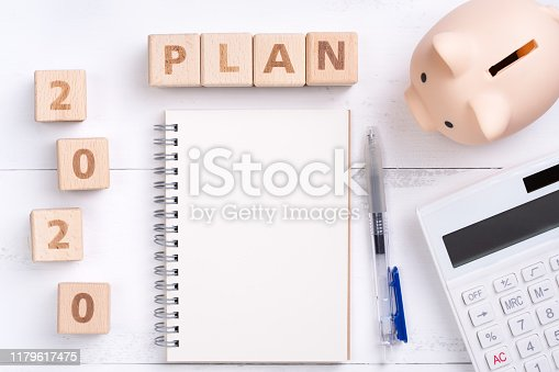 1170746979istockphoto 2020 goal, finance plan abstract design concept, wood blocks on white table background with piggy bank and calculator. 1179617475