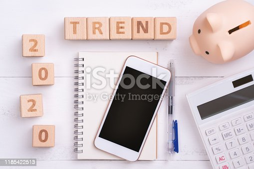 1170746979istockphoto 2020 goal, finance plan abstract design concept, wood blocks on white table background with piggy bank, cell phone. 1185422513