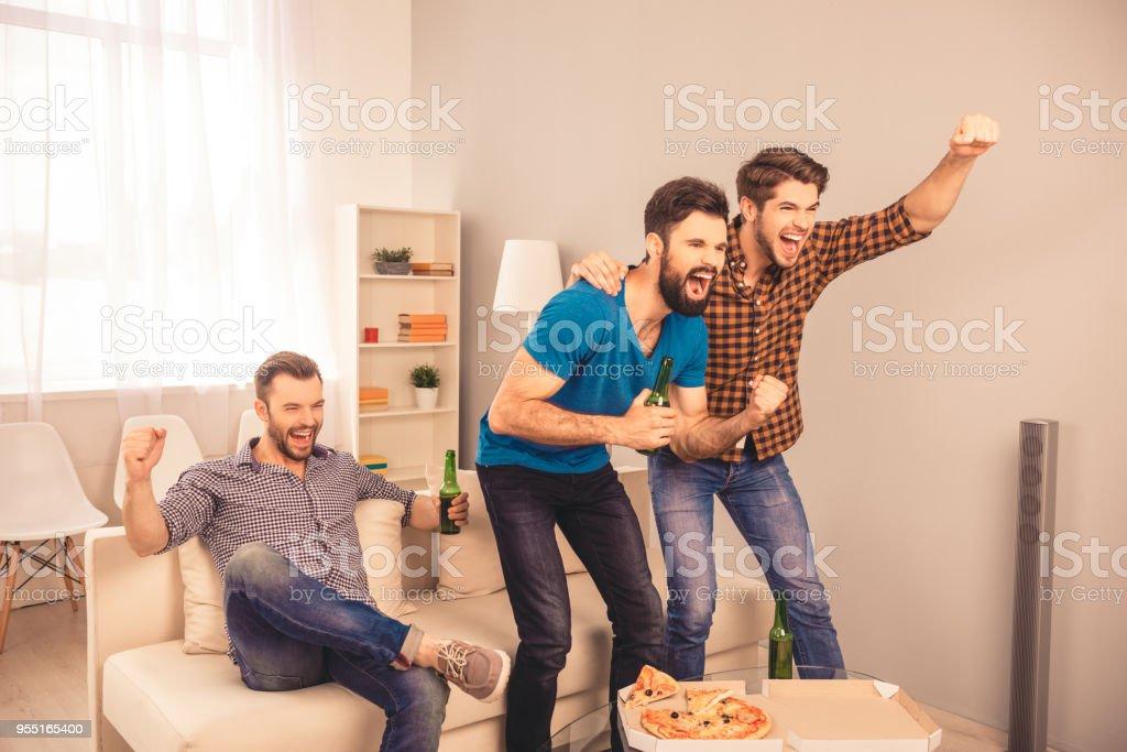 ¡Gol!  los hombres alegres felizes sentado en sofá y viendo sport tv con cerveza y pizza - foto de stock