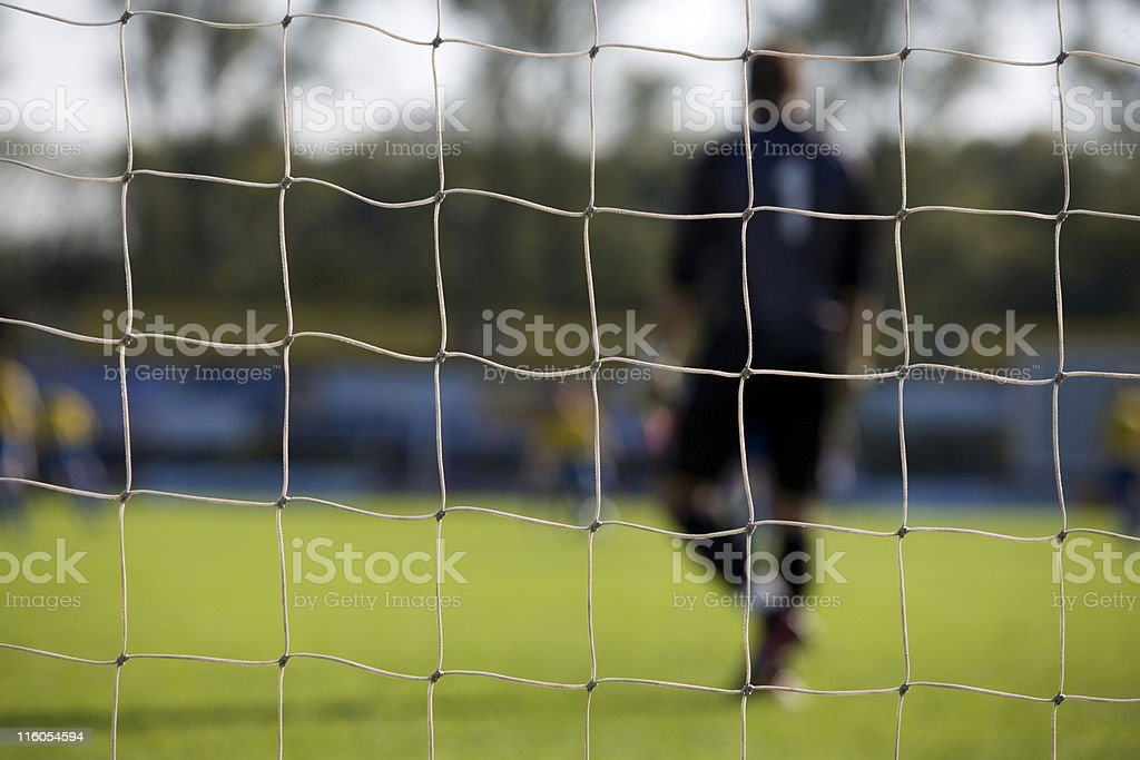 goal net and a goalkeeper out of focus royalty-free stock photo