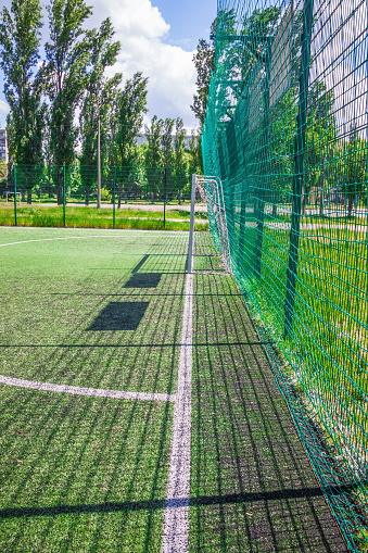 Goal on a football field with artificial green grass near the school. Amateur football field. Sunny summer day