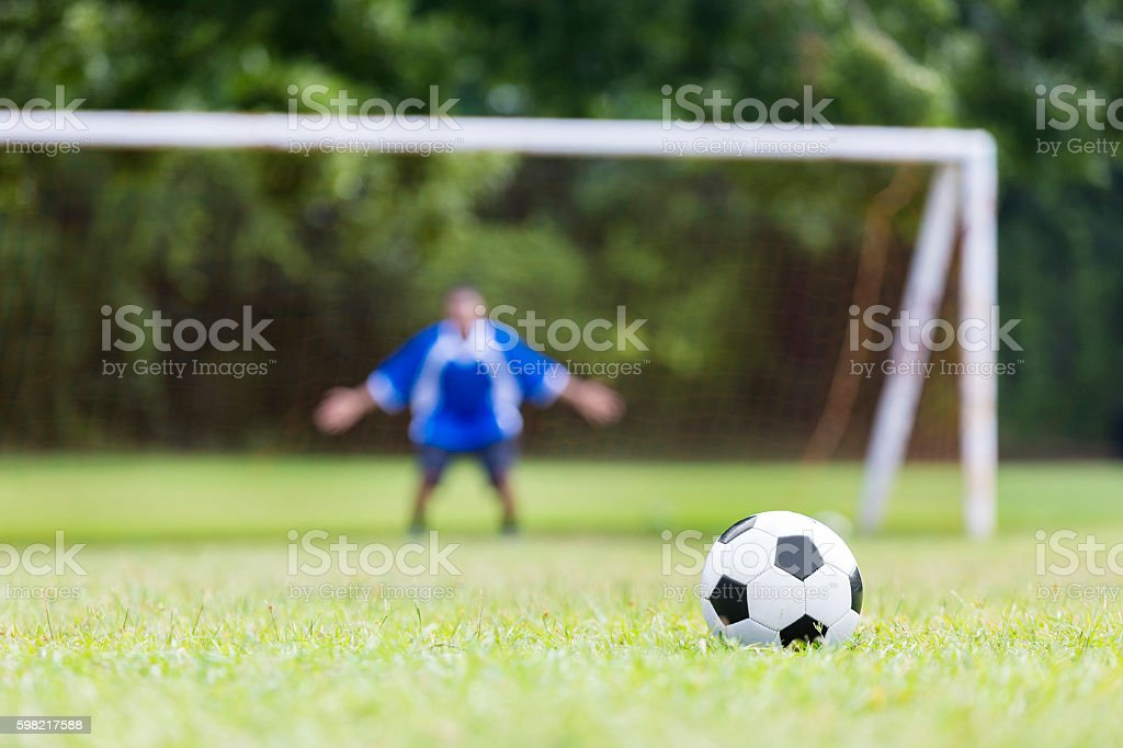 Goalie prepares to defend goal during soccer game stock photo